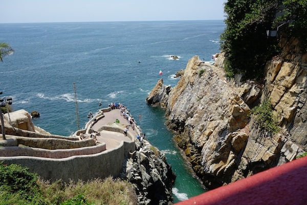 Before their dives, the divers have to swim across and climb the cliff