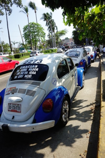 Blue-and-white VW bugs are taxis.