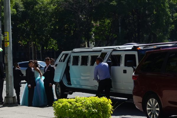 Girl in ball gown with young male attendants, and a stretch Hummer limo.