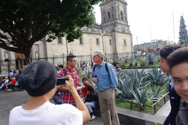 Doug helps a srudent from the Politecnico with his homework. Students sought us out several times, and filmed each other on their phones asking us questions like What is your favorite Mexican food' and What is your father's name. How do you suppose they recognized us as tourists?