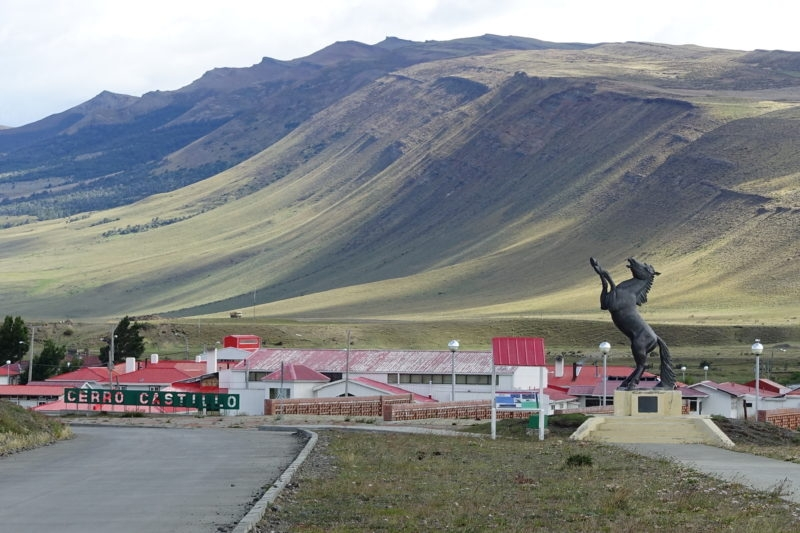 Village, flatlands rising to mountains, horse statue.